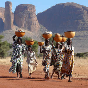 This runner-up image shows women from the Peul tribe in Mali carrying large bowls containing clothing and milk on their heads.