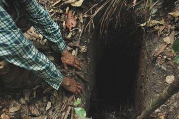 FUNAI field workers find a hole dug in the Amazon forest by the uncontacted Indian 'Last of his tribe', which he used to trap animals when hunting, Tanaru territory, Rondônia state, Brazil.