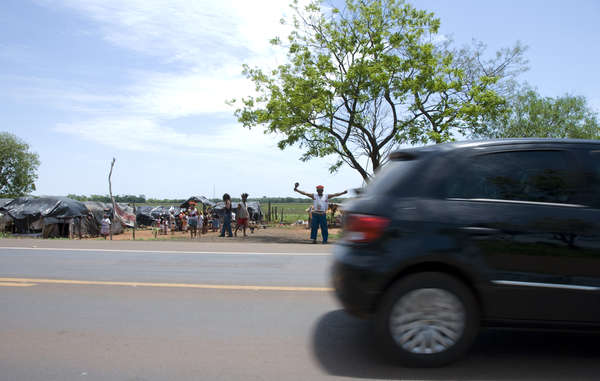 Guarani people have been forced to live by the side of the road in squalid conditions as their land has been taken illegally by cattle ranchers and sugar cane plantations.