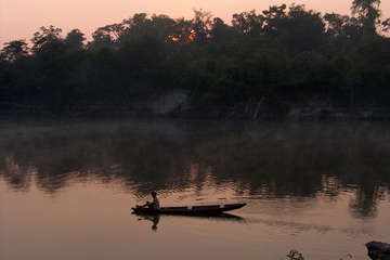 Pirahã man paddles by sundown on the Maici river. The tribe are at risk from plans for the Madeira River dams.