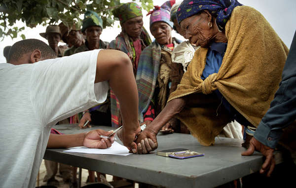 At the monthly food distribution in New Xade the mainly illiterate Bushmen sign a rosta with a thumbprint before collecting their allocated provisions.