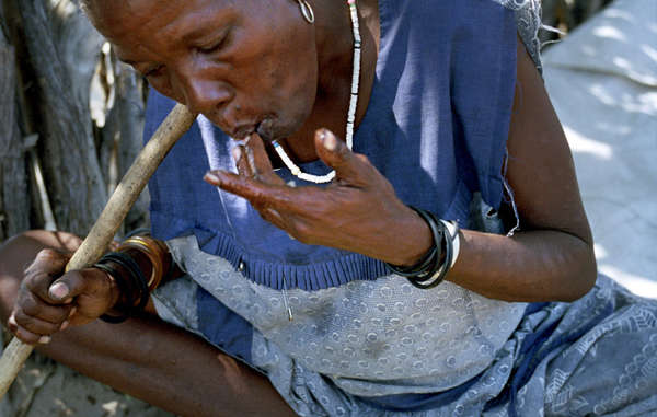 A Bushman woman chews the flesh of a melon for it's moisture in the village of Metsiameneng. Melons are cultivated by the Bushmen and provide a source of water, especially useful during the years that the government denied them access to boreholes.