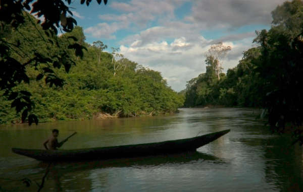 A Yanomami boy paddles his canoe back to his village in the Brazilian Amazon.