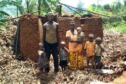 A family stand amidst the ruins of their home