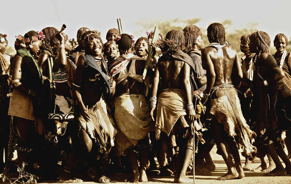 Excited Hamar women blowing their horns and shouting taunts to the Maza men who will whip them. Women regard the scars as a proof of devotion to their husbands. 