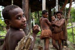 Eine Familie vom Volk der Kombai unter ihrem Stelzenhaus