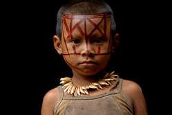 Un niño nukak lleva un collar hecho de dientes de mono.