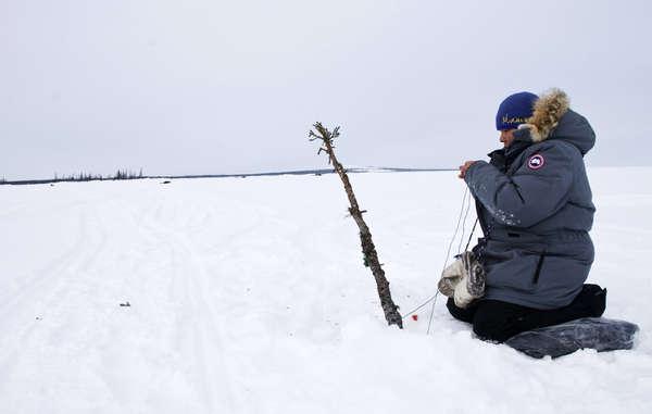 Eine Innu-Frau hat tiefe Löcher in das Eis gebohrt, um nach Seeforellen zu fischen.