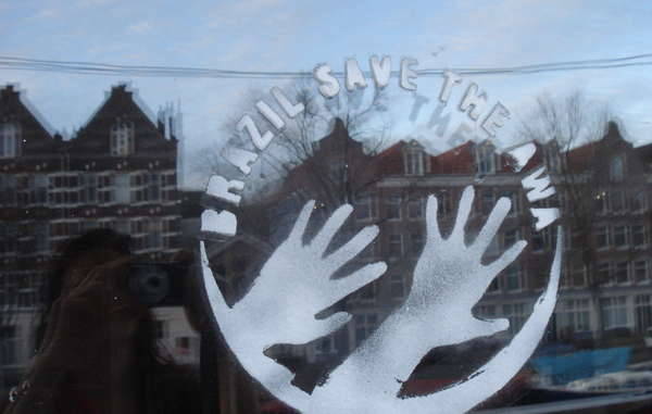 Il logo 'Salva gli Awá' su una vetrina ad Amsterdam.