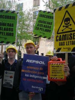 Manifestantes en Madrid con pancartas y cascos de obra denuncian las consecuencias letales de Camisea para los indígenas aislados.