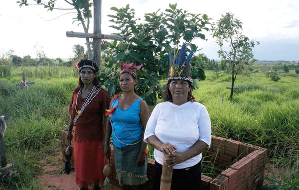 Members from the Takuara community stand by the grave of Marcos Veron, the Guarani leader of this community who was beaten and killed by ranchers' gunmen, while attempting to peacefully return to his land in 2003.