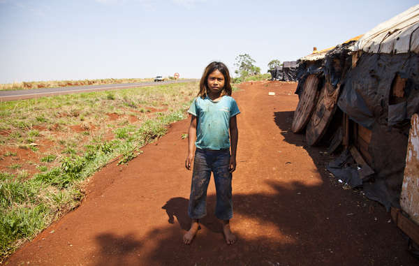 A Guarani girl stands by her road-side shack – endless fields have replaced her tribe's rich forests. Children as young as nine have been committing suicide.