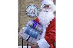 Der Weihnachtsmann überreicht Flaschen mit Wasser an Botswanas Hochkommissariat in London. © M. Cowan/Survival