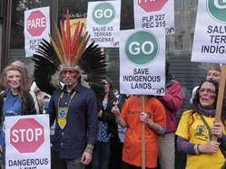 """Protestors held placards telling Brazil to stop dangerous laws and save indigenous lands."""
