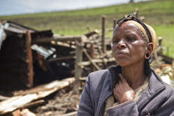 An Ogiek woman sits in front of the remains of her demolished house.