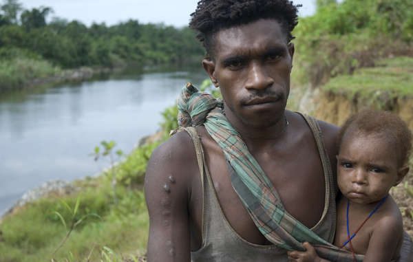 Ein Korowai-Mann mit Kind in West-Papua.