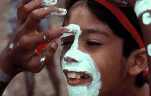 Aplicación de la pintura de cara tradicional a un joven aborigen, festival de danza, norte de Queensland, Australia.