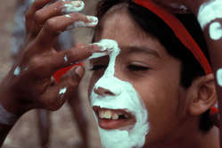 Applying traditional face paint to an Aboriginal boy during a dance festival in Northern Queensland.