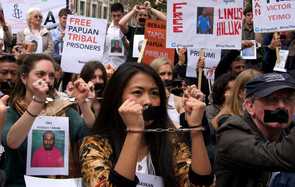 """The protestors outside the Indonesian embassy were handcuffed and had their mouths taped shut."""