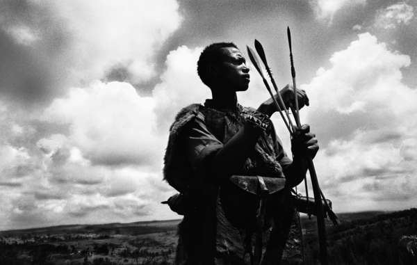 An Ogiek man prepares his bow and arrows.