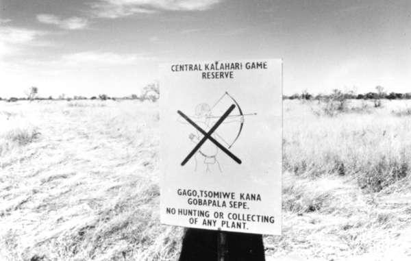 Cartel situado en la entrada de la Reserva de Caza del Kalahari Central que prohíbe a los bosquimanos cazar. Botsuana, 1989.