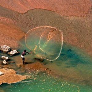 Cette image splendide montre un pêcheur santhal du Bengale occidental, en Inde, qui lance son filet.