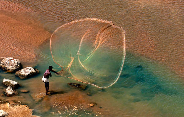 """This stunning image shows a Santhal fisherman in West Bengal, India, casting his net."""