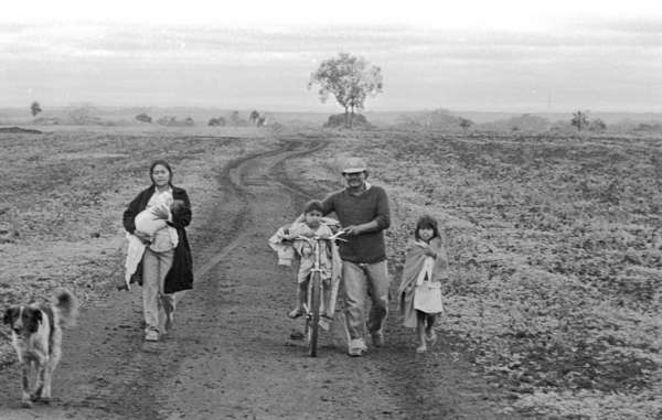 Guarani family walking on their land.
