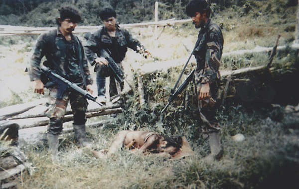 For decades, West Papua's tribal people have suffered at the hands of the Indonesian military. This 'trophy' photograph was taken by soldiers, in the same year as the Biak massacre, after they killed a man and his 12 year old nephew.