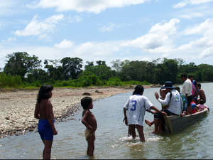 A boat carrying local people stops on the riverbank near the Mashco-Piro. The Mashco-Piro children have put on the clothes they have been given.