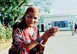 A Bushman woman dances in the street outside the court in Lobatse after the verdict