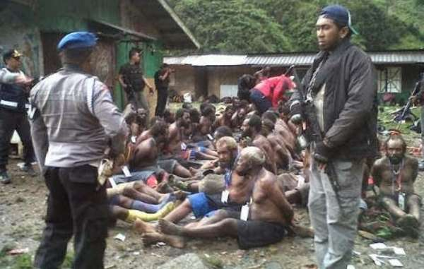 Papuan villagers were stripped to their waists and had their hands tied behind their backs before being interrogated by police.