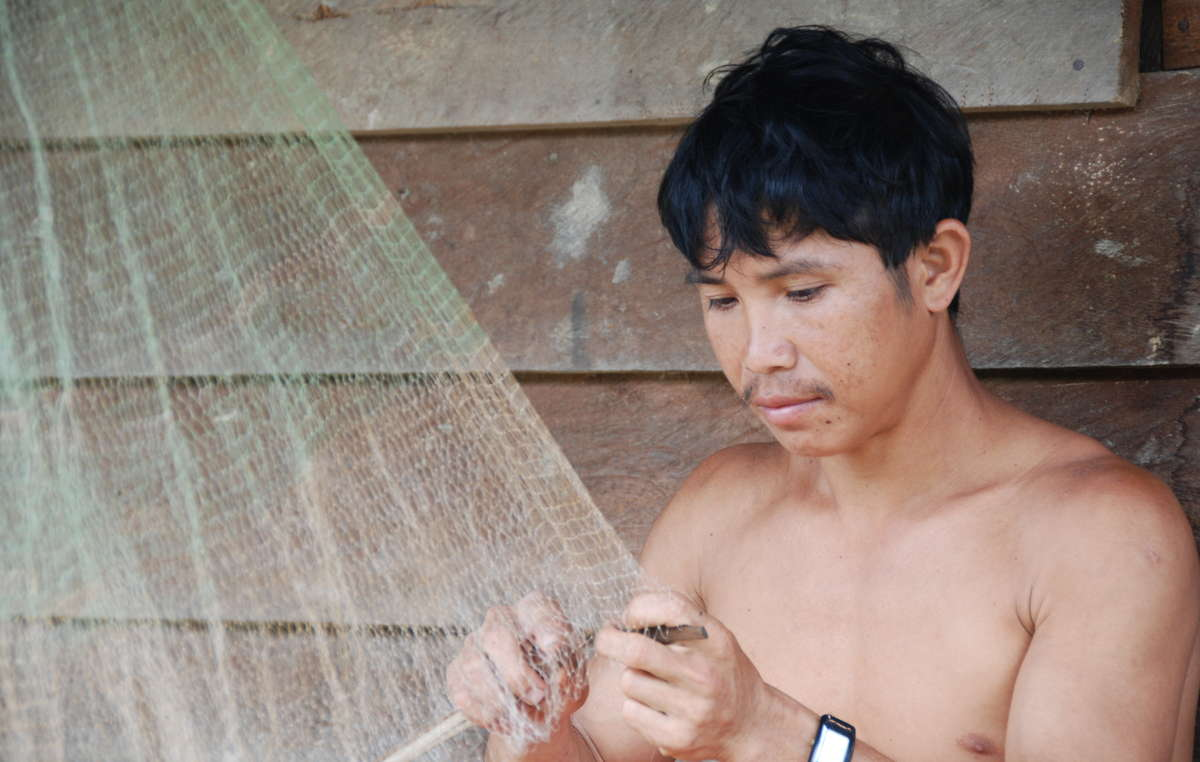 Penan man from Ba Pakan fixing his fishing net. The Penan's rivers are being polluted by the logging and plantation industries, killing fish and preventing some communities from accessing safe drinking water.