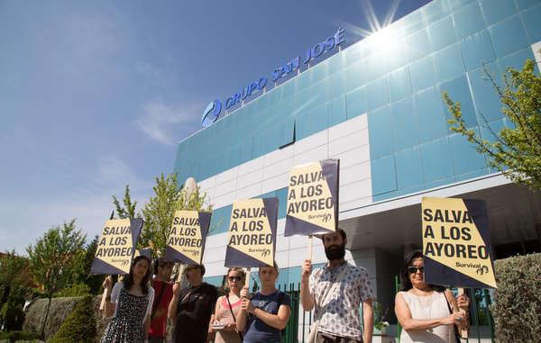 Manifestantes sujetan pancartas con el mensaje 'Salva a los ayoreo' durante la Junta General de Accionistas de la empresa española Grupo San José.