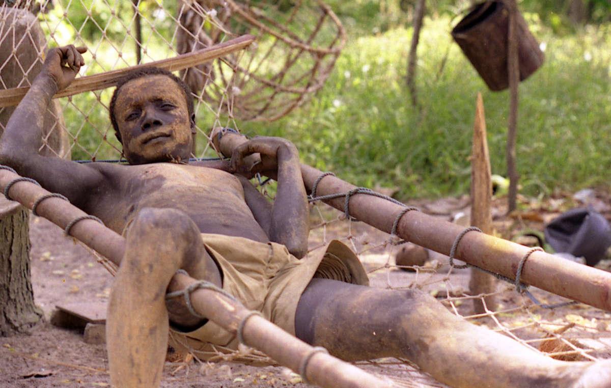 Ein Mann des Onge-Volkes in einer Hängematte, Andamanen-Inseln, Indien.
