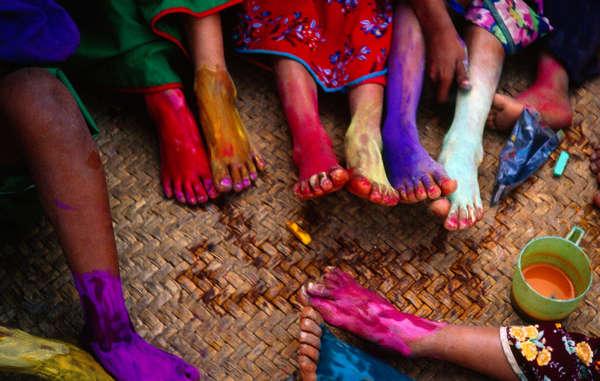 Ragazzi e ragazze huicol del Messico si colorano i piedi con gesso e colori in polvere.
