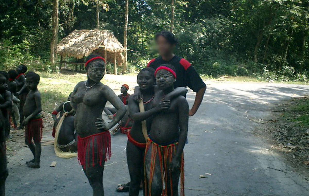 A tourist poses with a group of Jarawa.
