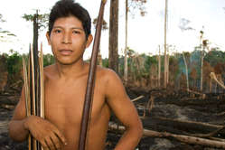 An Awá man stands amidst the burnt remains of his tribes forest