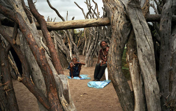 An elderly Bushman couple in their fenced yard in New Xade, the government resettlement camp to which many Bushmen have been relocated in the last ten years.