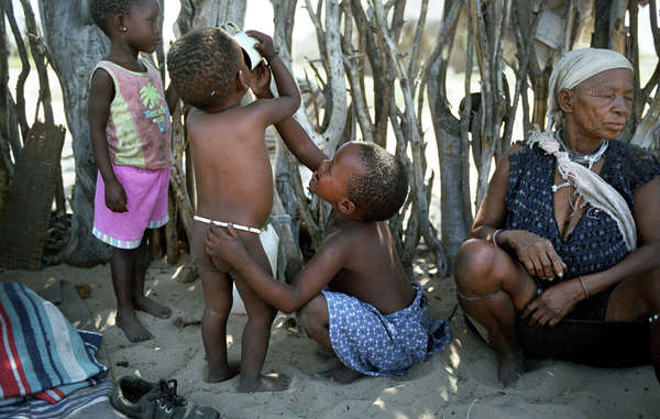 Young children drink water from a distant borehole in Metsiamenong, Botswana. The Bushmen have since won a court appeal to access water on their ancestral lands.