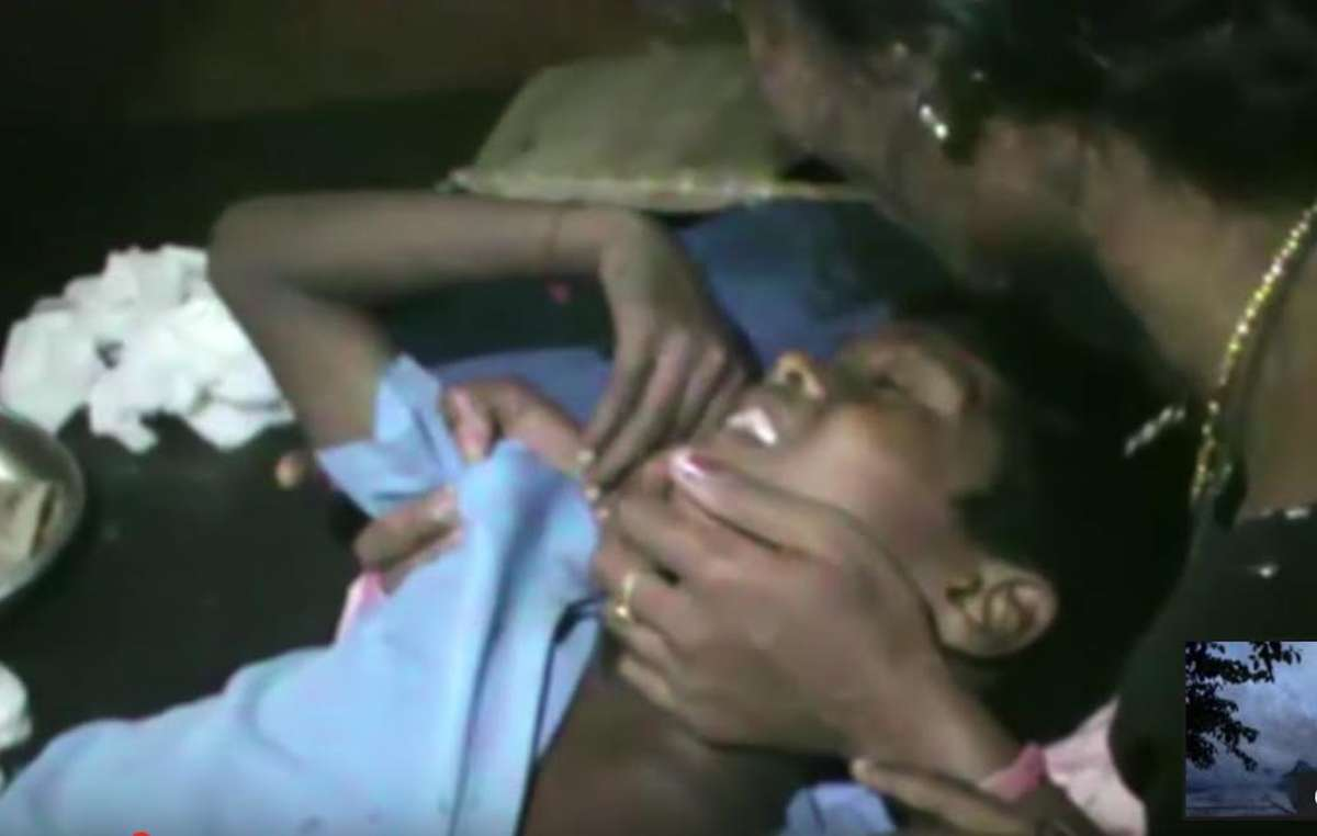 Akash Orang is comforted by his mother after being shot by a park guard. He is now maimed for life.