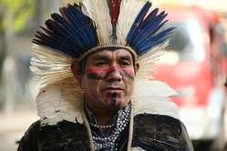 """""""El activista guaraní Ládio Veron junto a manifestantes ante la Embajada de Brasil en Londres exigen que se respeten los derechos territoriales de los guaraníes."""""""