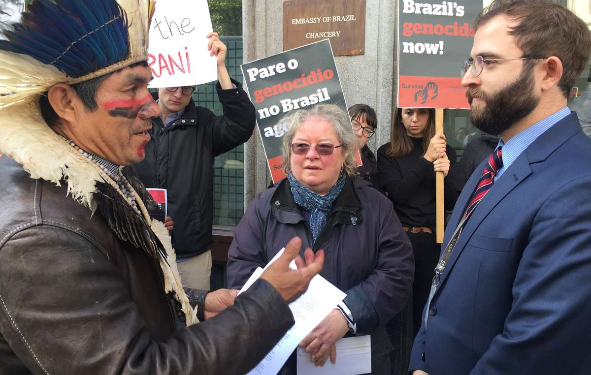 Brazilian tribal leader Ladio Veron hands a letter demanding land rights to an embassy official