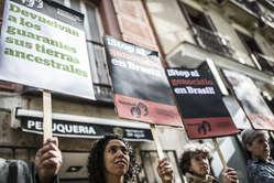 Activistas portan pancartas contra el robo de tierras indígenas ante la Embajada de Brasil en Madrid.