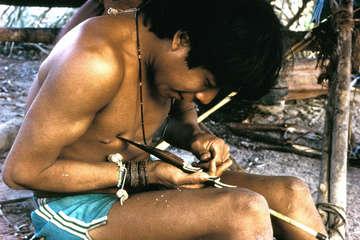 Mann der Urueu Wau Wau schnitzt einen Bogen