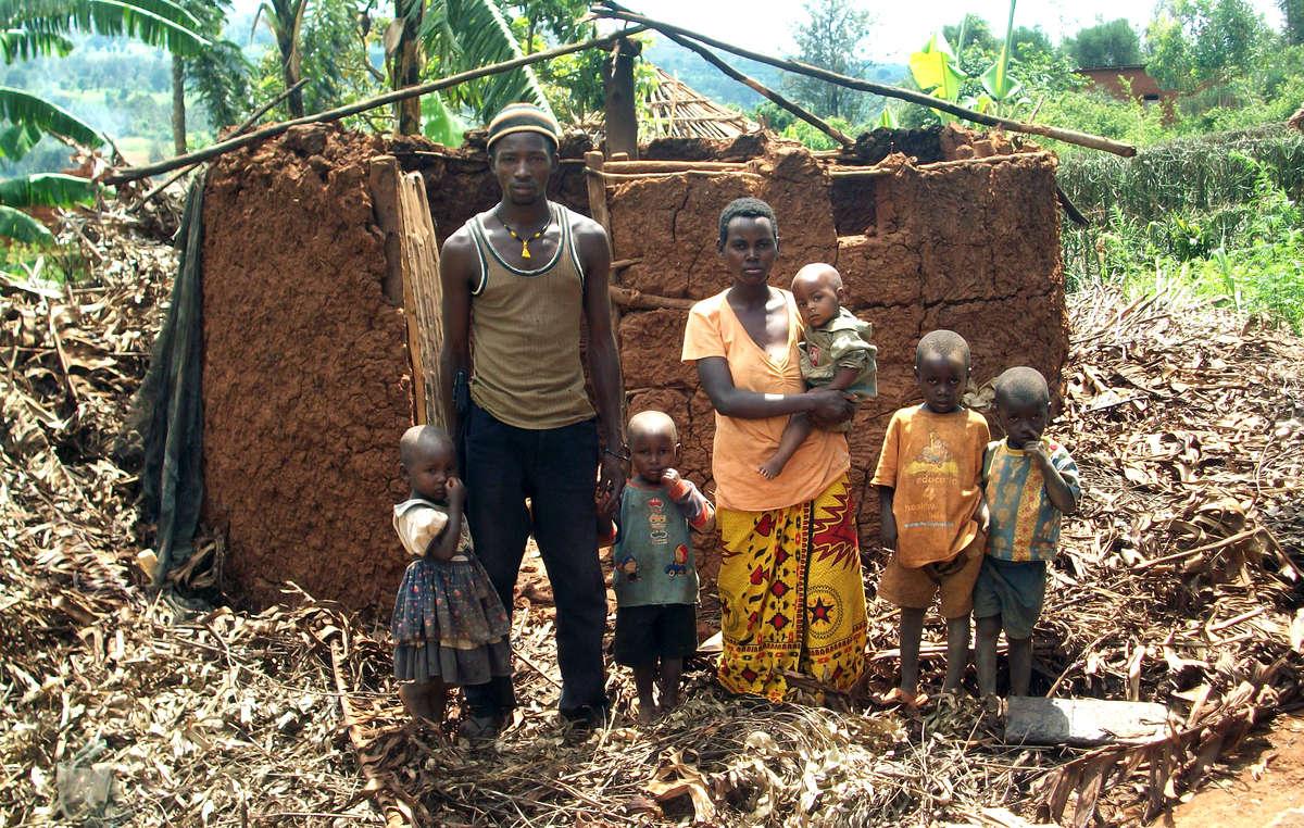Eine Batwa-Familie steht inmitten ihres zerstörten Hauses.