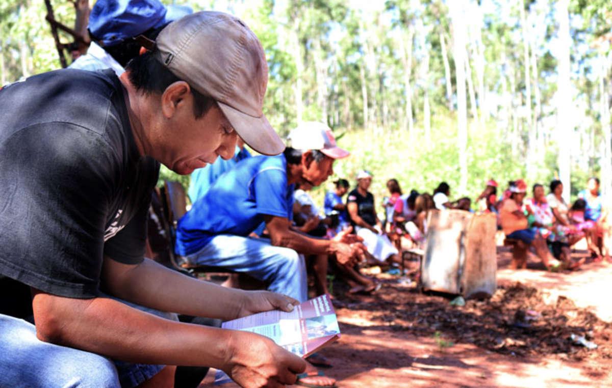 Bei einem Treffen der Gemeinde liest ein Guarani-Mann einen Flyer von Survival International, der globalen Bewegung für indigene Völker. Survival arbeitet seit den 70er-Jahren für die Guarani.