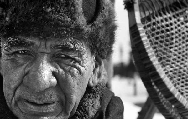 Elder Shoashim Nui, the community's most skilled carpenter, beside a pair of his renowned snowshoes.