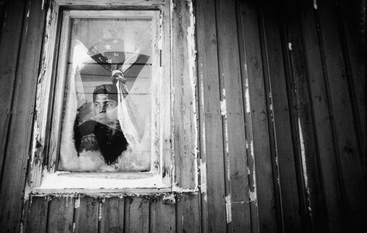 A young Innu looks out from one of the government buildings they have been forced to settle in.