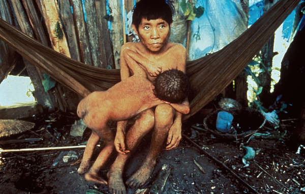 Yanomami mother and child, in a community where disease has struck caused by the invasion of gold miners, 1990.